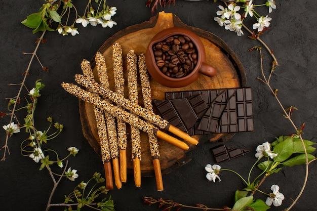 Bovenaanzicht snoep sticks chocolade koffie zaden op het bruine bureau en donker