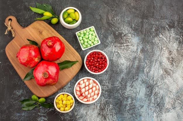Bovenaanzicht snoepjes drie granaatappels met bladeren op het bord vijf kommen snoep