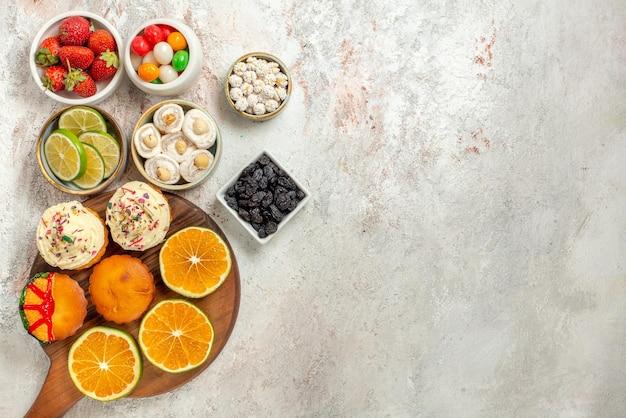 Bovenaanzicht snoepjes in kommen zes kommen bessen snoep en turks fruit naast het bord met plakjes sinaasappel en koekjes op de witte tafel