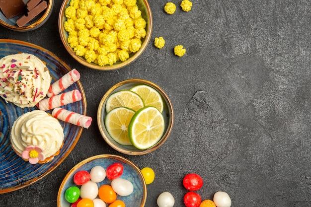 Bovenaanzicht snoepjes op tafel blauwe schotel van cupcakes en kommen chocolade limoenen kleurrijke snoepjes aan de linkerkant van de tafel