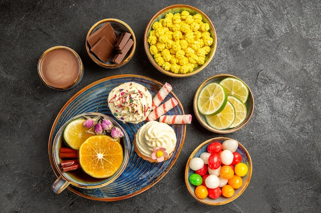 Bovenaanzicht snoepjes op tafel kommen van chocolade citrusvruchten chocolade crème kleurrijke snoepjes en een bord cupcakes en een kopje thee met citroen op de donkere tafel