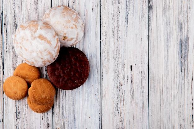 Bovenaanzicht snoepjes vanille koekjes chocolade koekjes en peperkoek aan de linkerkant met kopie ruimte op witte houten achtergrond