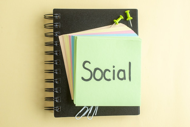 Bovenaanzicht sociale schriftelijke notitie samen met kleurrijke kleine aantekeningen op papier op lichte achtergrond voorbeeldenboek kladblok kleur schoolbaan kantoorwerk