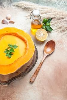 Bovenaanzicht soep fles olie citroen lepel pompoensoep met kruiden op het bord