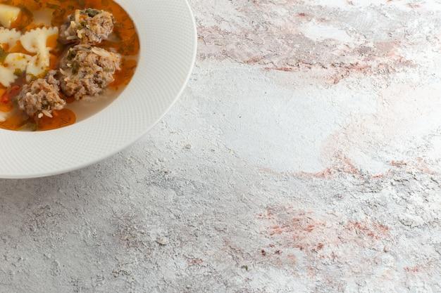 Bovenaanzicht soep met vlees heerlijke soep met pasta en vlees op witte ondergrond