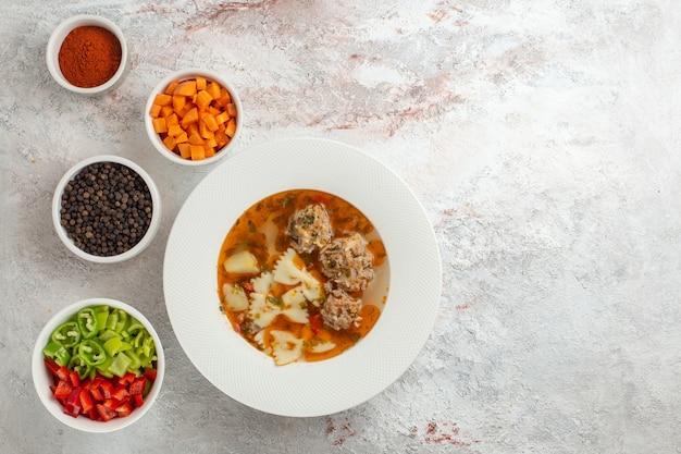 Bovenaanzicht soep met vlees smakelijke soep met gesneden groenten en verschillende kruiden op witte achtergrond