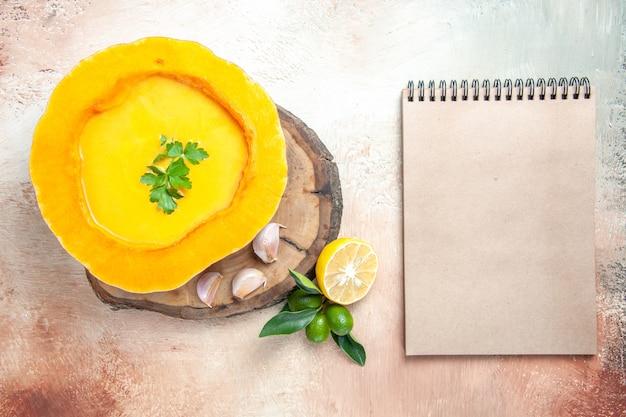 Bovenaanzicht soep pompoensoep met kruiden knoflook citroen crème notitieboekje