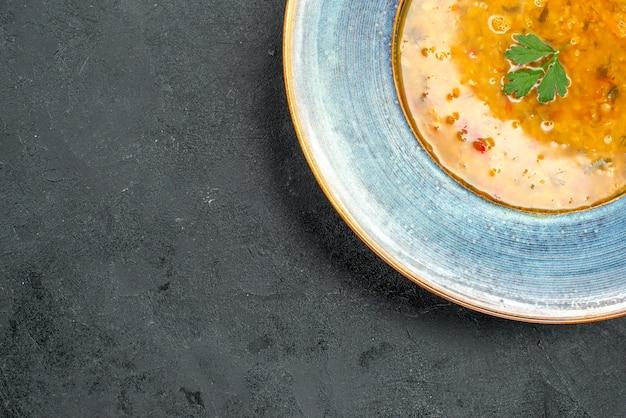 Bovenaanzicht soep soep met kruiden in de blauwe kom op tafel