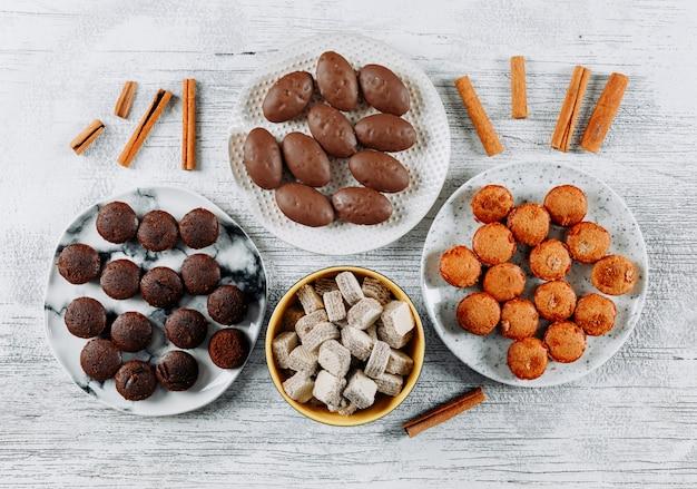 Bovenaanzicht soorten cookies in platen op witte houten