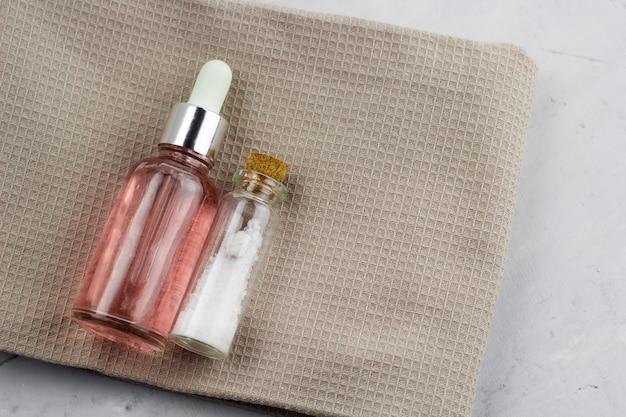 Bovenaanzicht spa set flessen op een handdoek op een marmeren tafel