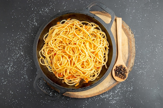 Bovenaanzicht spaghetti koekenpan zwarte peper in houten lepel op houten bord op donkere achtergrond