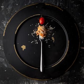 Bovenaanzicht spaghetti met vork en tomaat en ricotta kaas in ronde zwarte plaat