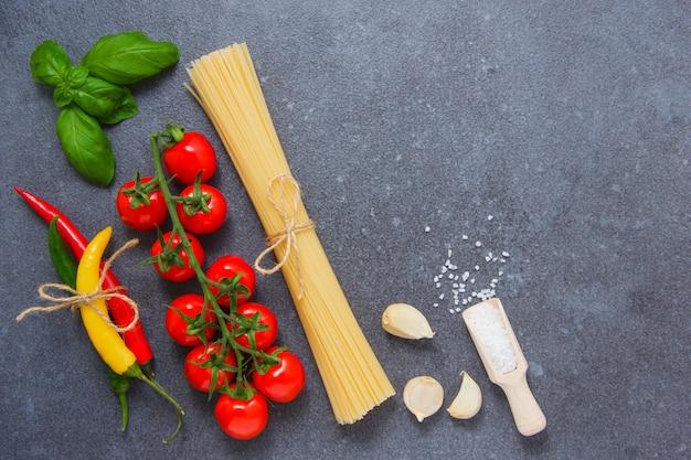 Bovenaanzicht spaghetti pasta met chili pepers, een tros tomaten, zout, zwarte peper, knoflook, bladeren op grijze achtergrond. ruimte voor tekst
