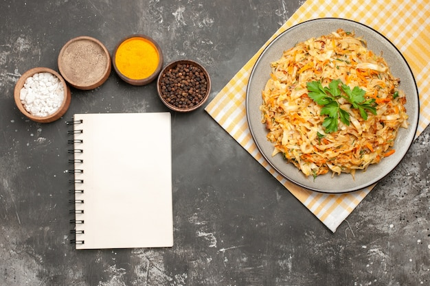 Bovenaanzicht specerijen plaat van kool op het geruite tafellaken specerijen witte notebook