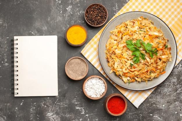 Bovenaanzicht specerijen plaat van kool op het geruite tafellaken witte notebook kleurrijke kruiden