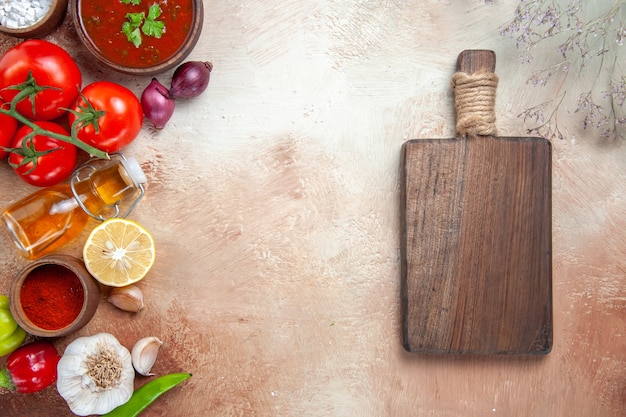 Bovenaanzicht specerijen specerijen fles olie tomaten citroensaus houten plank