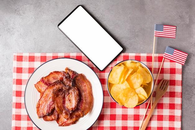 Bovenaanzicht spek op plaat met chips en lege telefoon