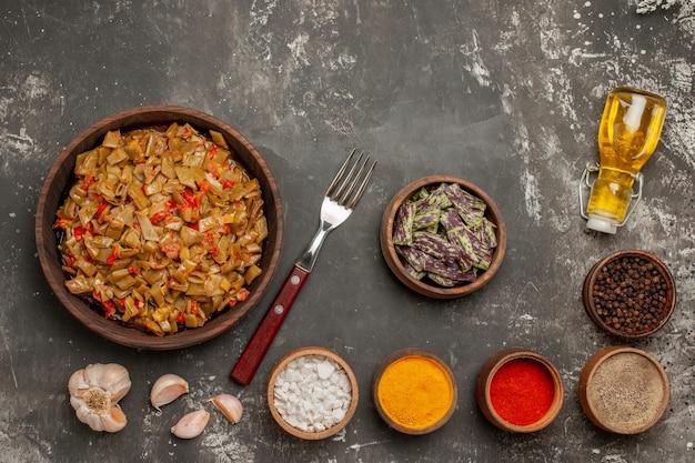 Bovenaanzicht sperziebonen kommen met kruiden en bord sperziebonen en tomaten naast de knoflookvorkfles olie op de donkere tafel