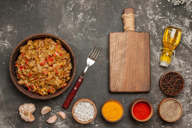 Bovenaanzicht sperziebonen, sperziebonen en tomaten naast de knoflookvorkfles olie de snijplank en kommen met kruiden op de donkere tafel