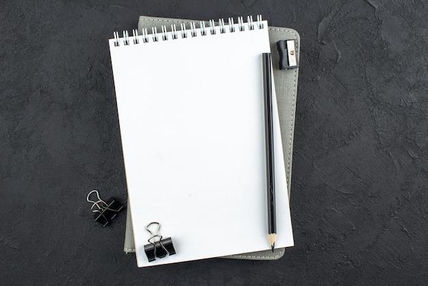 Bovenaanzicht spiraal notebook zwarte pen bindmiddel clips puntenslijper op donkere achtergrond