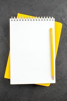 Bovenaanzicht spiraal notitieblok geel potlood op zwart