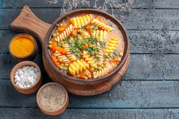Bovenaanzicht spiraal pastasoep heerlijke maaltijd met verschillende smaakmakers op donkere vloer soep kleur italiaanse pastaschotel keuken