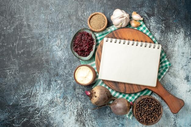 Bovenaanzicht spiraalvormig notitieblok op houten plankkruiden in kommen knoflookbieten op grijze tafel met vrije ruimte
