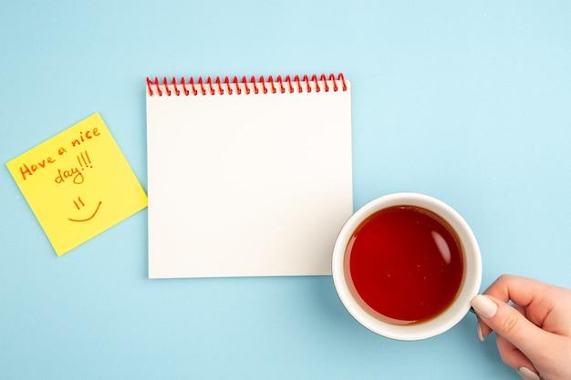 Bovenaanzicht spiraalvormig notitieboekje kopje thee in vrouwelijke hand fijne dag geschreven op geel notitiepapier op blauw