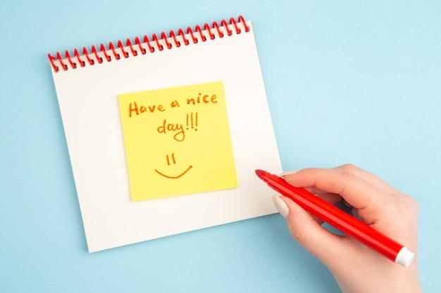 Bovenaanzicht spiraalvormig notitieboekje vrouwelijk handschrift fijne dag op gele plaknotitie op blauw