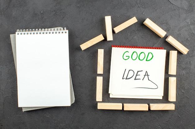 Bovenaanzicht spiraalvormige notebook huis vormige houtblokken goed idee geschreven op notebook op zwarte tafel