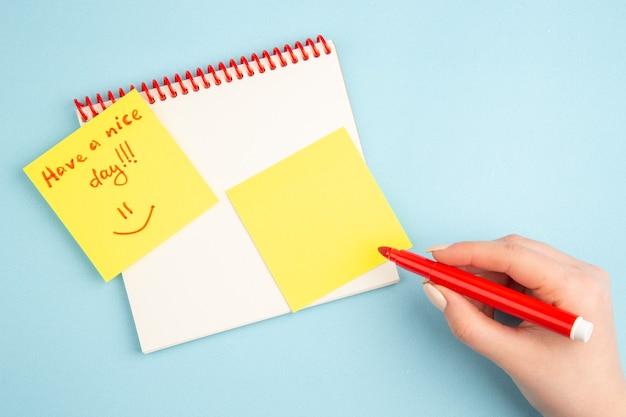 Bovenaanzicht spiraalvormige notitieboekje rode markering in de hand van de vrouw een fijne dag geschreven op geel notitiepapier op blauw