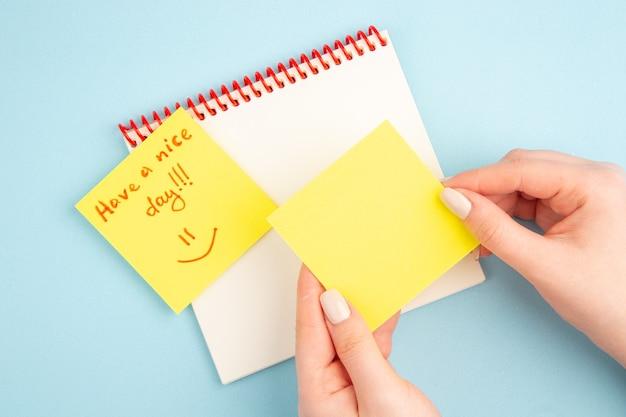 Bovenaanzicht spiraalvormige notitieboekjes in de hand van de vrouw fijne dag geschreven op geel notitiepapier op blauw