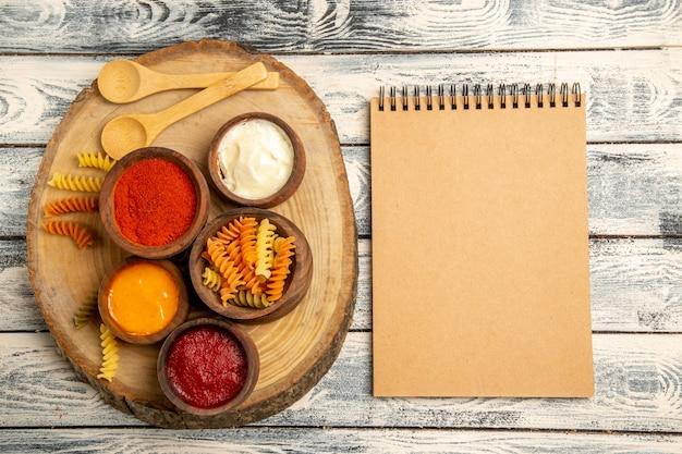 Bovenaanzicht spiraalvormige pasta met verschillende kruiden op grijs bureau