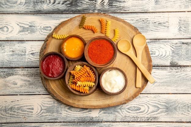 Bovenaanzicht spiraalvormige pasta met verschillende kruiden op het grijze rustieke bureau