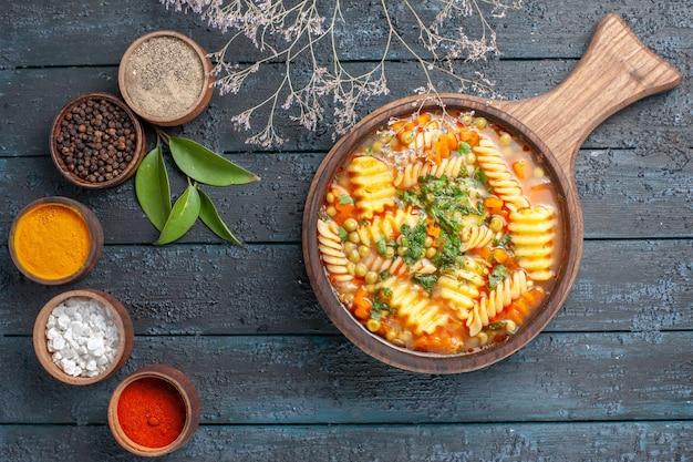 Bovenaanzicht spiraalvormige pastasoep met verschillende smaakmakers op donkerblauwe bureausoepkleur italiaanse pastaschotelkeuken