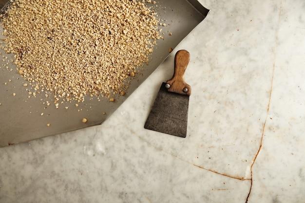 Bovenaanzicht, stalen plaat met geraspte hazelnoten op gebroken oude marmeren tafel binnen professionele ambachtsman