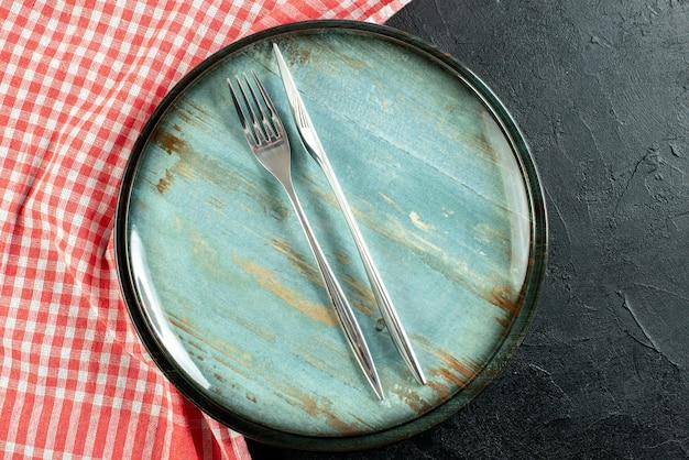 Bovenaanzicht stalen vork en diner mes op ronde schotel rood en wit geruit tafelkleed op zwarte tafel