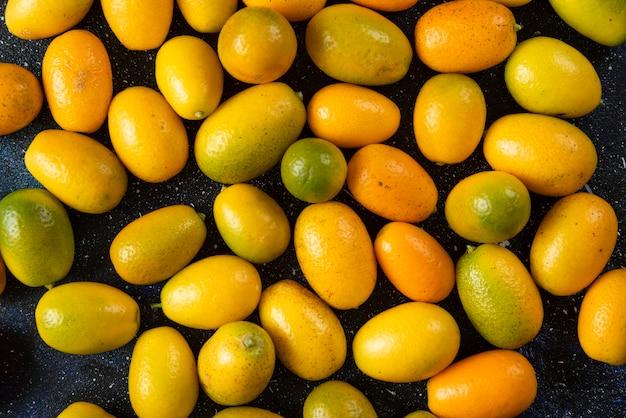 Bovenaanzicht. stapel kumquats over blauw oppervlak