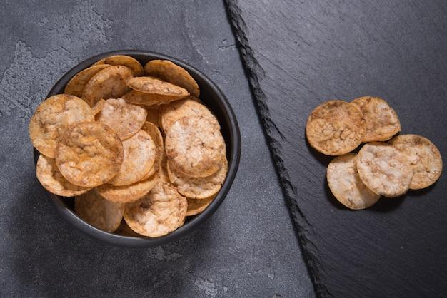 Bovenaanzicht stapel van organische, knapperige, gebakken, volkoren rijst chips met kruiden. glutenvrije gezonde snack. voedsel achtergrond