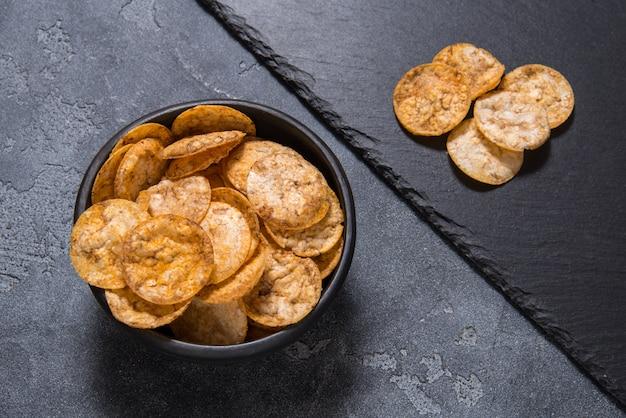 Bovenaanzicht stapel van organische, knapperige, gebakken, volkoren rijst chips met kruiden. glutenvrije gezonde snack. zwarte keramische kom op grijze stenen achtergrond