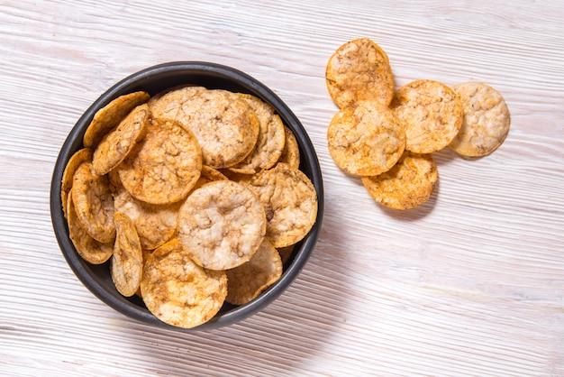Bovenaanzicht stapel van organische, knapperige, gebakken, volkoren rijst chips met kruiden. glutenvrije gezonde snack. zwarte keramische kom op houten achtergrond