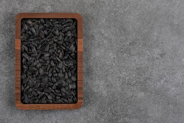 Bovenaanzicht. stapel zonnebloempitten in houten kom over grijs oppervlak.