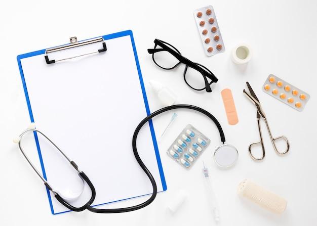 Bovenaanzicht stethoscoop met brillen en medicijnen