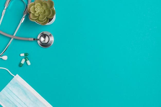 Bovenaanzicht stethoscoop met gezichtsmasker op tafel