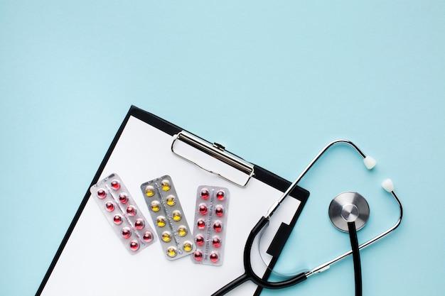 Bovenaanzicht stethoscoop met pillen op kladblok