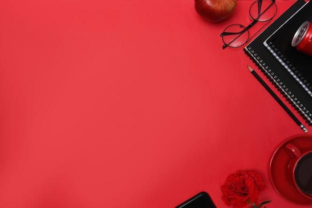 Bovenaanzicht stijlvolle werkplek met notebook, bril, koffiekopje, mobiele telefoon en pen op rode achtergrond.