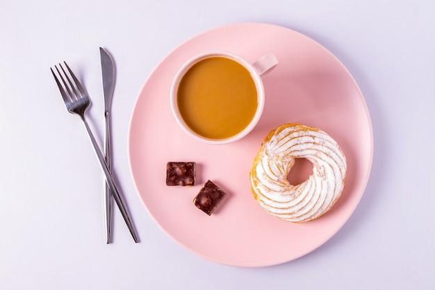 Bovenaanzicht stilleven van cake op een roze bord, bestek en kopjes met cacao of koffie met melk. selectieve aandacht, horizontale oriëntatie.