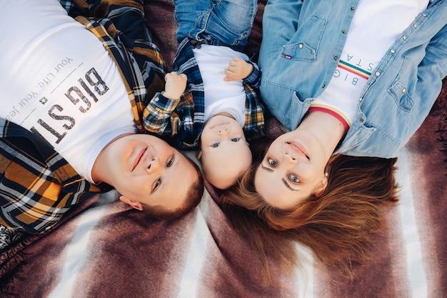 Bovenaanzicht stockfoto van een gelukkig jong gezin van moeder, vader en peuterzoon die lacht naar de camera die op bed ligt.