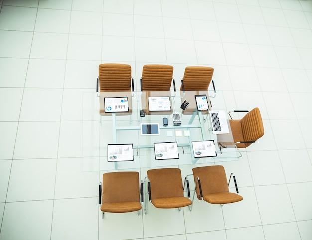 Bovenaanzicht - stoelen en bureau met documenten en laptop voor onderhandelingen met zakenpartners. de foto is een lege ruimte voor uw tekst