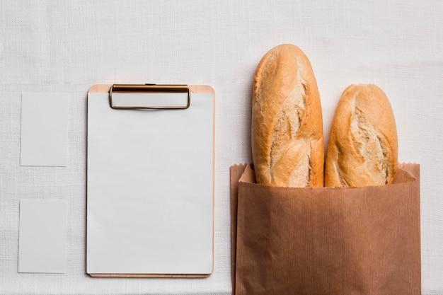Bovenaanzicht stokbrood met leeg klembord